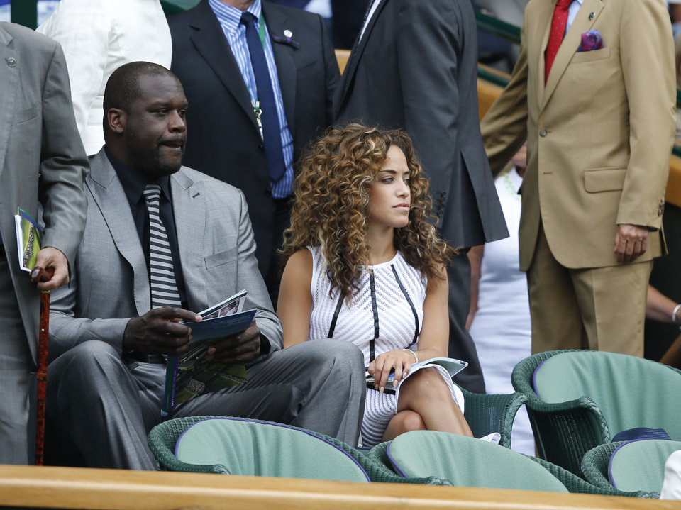 Photo - US retired basketball player Shaquille O'Neal, left, watches a play on centre court during the first day at the All England Lawn Tennis Championships in Wimbledon, London,  Monday, June  23, 2014. (AP Photo/Pavel Golovkin)