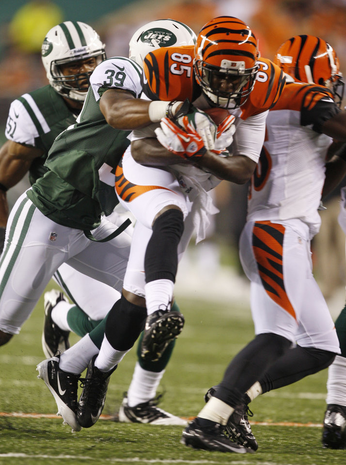 Photo -   Cincinnati Bengals wide receiver Armon Binns (85) is tackled by New York Jets strong safety Antonio Allen (39) during the first half of an NFL preseason football game, Friday, Aug. 10, 2012, in Cincinnati. (AP Photo/David Kohl)