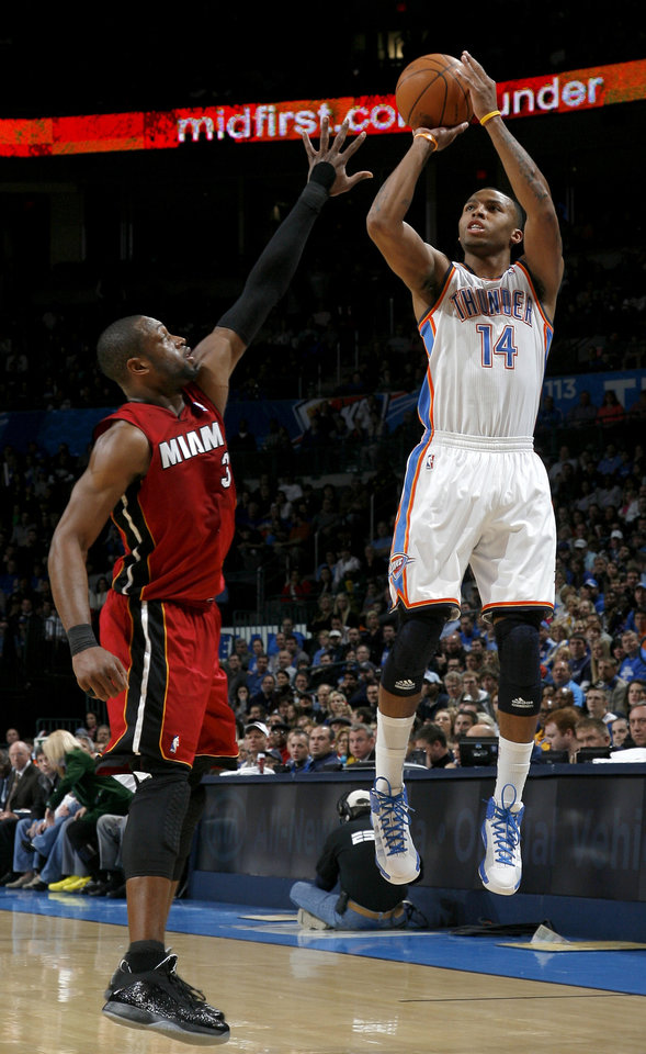 Photo - Oklahoma City's Daequan Cook (14) shoots as Miami's Dwyane Wade (3) defends during the NBA basketball game between Oklahoma City and Miami at the OKC Arena in Oklahoma City, Thursday, Jan. 30, 2011. Photo by Sarah Phipps, The Oklahoman