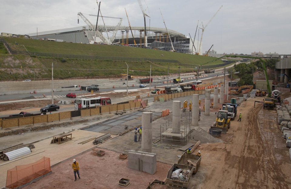 Photo - Men work on the construction of a bus terminal near the Itaquerao stadium in Sao Paulo, Brazil, Wednesday, April 9, 2014. Construction continues in and around the stadium that is slated to host the World Cup opener match between Brazil and Croatia on June 12. (AP Photo/Andre Penner)