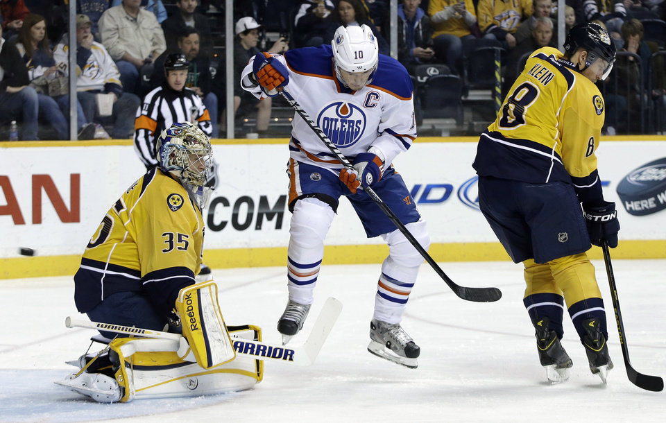 Photo - Edmonton Oilers center Shawn Horcoff (10) jumps out of the way of a shot by teammate Corey Potter, unseen, that gets by Nashville Predators goalie Pekka Rinne (35), of Finland, for a goal in the first period of an NHL hockey game on Monday, March 25, 2013, in Nashville, Tenn. Also defending for the Predators is Kevin Klein (8). (AP Photo/Mark Humphrey)