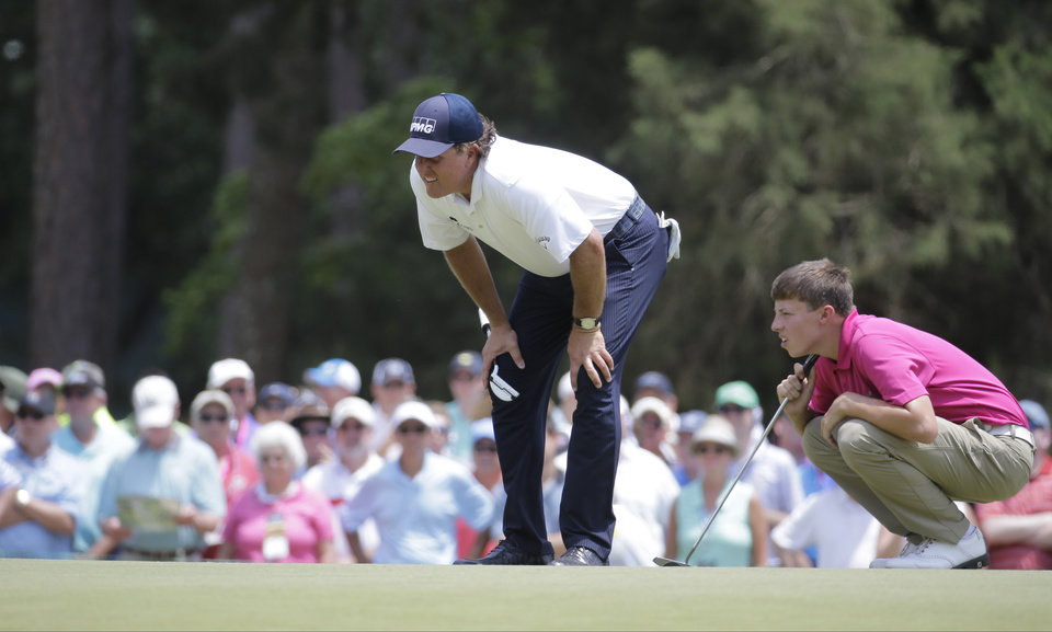 Photo - Phil Mickelson, left and Amateur, Matthew Fitzpatrick, England, line up their putts on the second hole during the second round of the U.S. Open golf tournament in Pinehurst, N.C., Friday, June 13, 2014. (AP Photo/Eric Gay)
