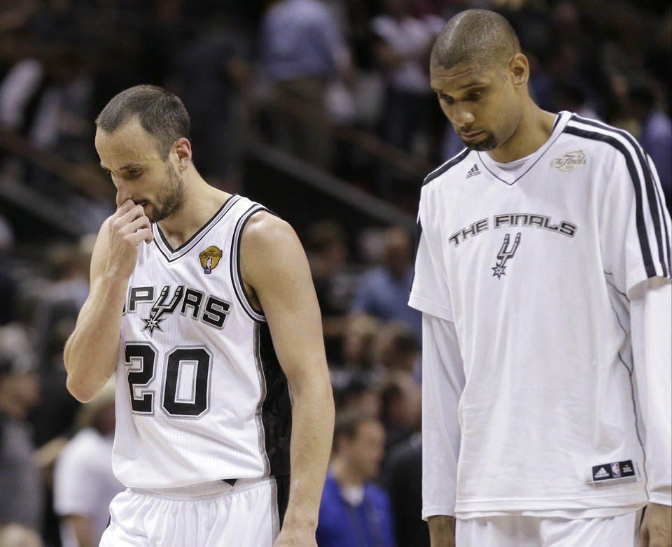 Photo - San Antonio Spurs' Manu Ginobili, of Argentina,, left, and Tim Duncan leave the floor after losing to the Miami Heat at Game 4 of the NBA Finals basketball series, Thursday, June 13, 2013, in San Antonio. The Heat won 109-93. (AP Photo/Eric Gay)