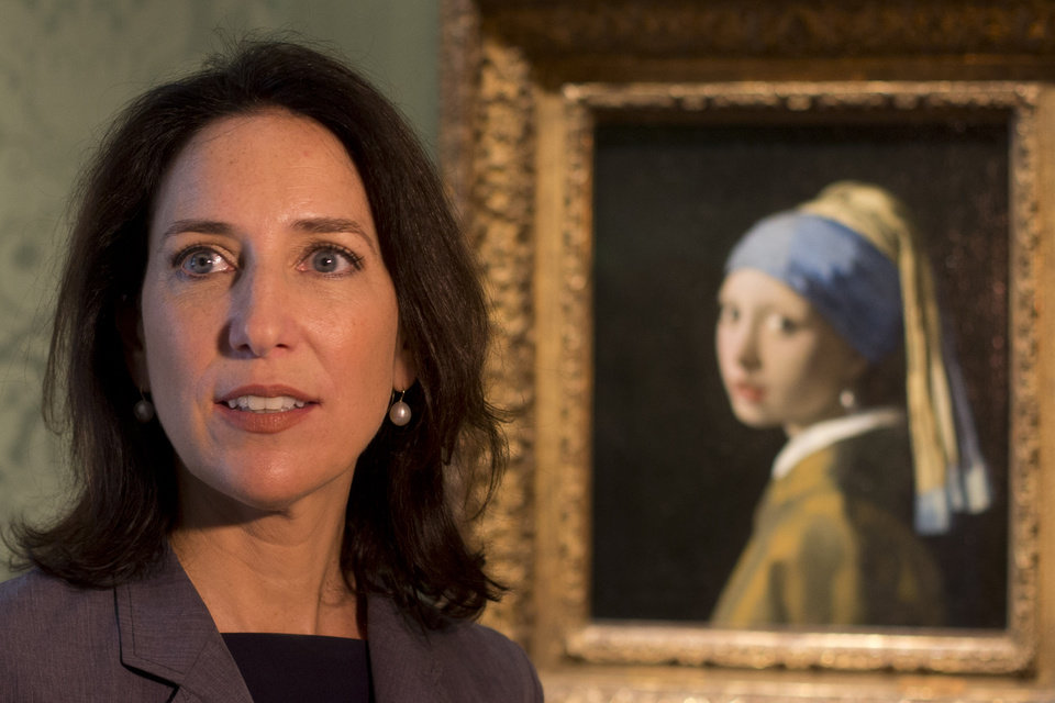 Photo - Director Emilie Gordenker is interviewed as she stands next to Johannes Vermeer's Girl with a Pearl Earring (painted approx. 1665) during a preview for the press in The Hague, Netherlands, Friday, June 20, 2014. The Mauritshuis reopens after a two-year renovation that allowed its masterpieces, including Vermeer's The Girl with the Pearl Earring to be seen by record-setting crowds abroad. The public will have access for free from 8 pm till midnight on Friday June 27th after the official ceremonial opening and from June 28 onwards the museum will revert to regular opening hours. (AP Photo/Peter Dejong)