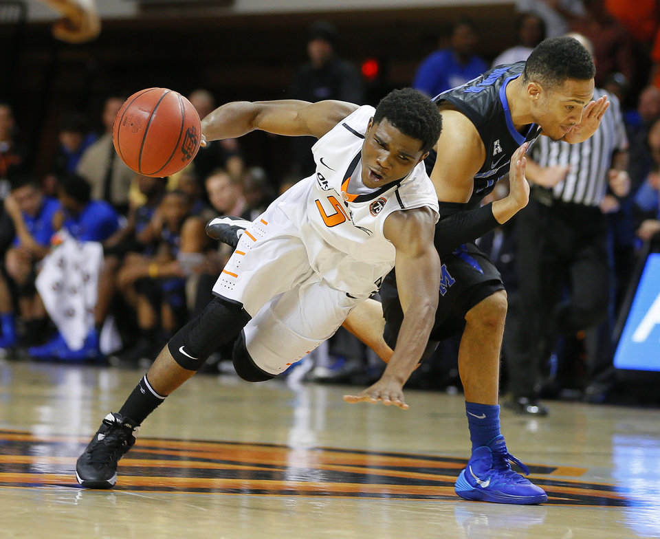 Photo - Oklahoma State's Stevie Clark (5) falls down as he runs into Memphis' Michael Dixon Jr. (11) during an NCAA college basketball game between Oklahoma State and Memphis at Gallagher-Iba Arena in Stillwater, Okla., Tuesday, Nov. 19, 2013. Photo by Bryan Terry, The Oklahoman