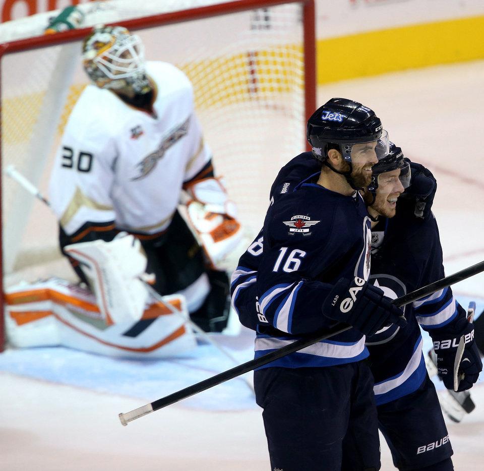 Photo - Winnipeg Jets' Andrew Ladd (16) and Bryan Little, right, celebrate after Ladd scored against Anaheim Ducks goaltender Viktor Fasth (30) during first period of NHL hockey action in Winnipeg, Manitoba, Sunday, Oct. 6, 2013. (AP Photo/The Canadian Press, Trevor Hagan)