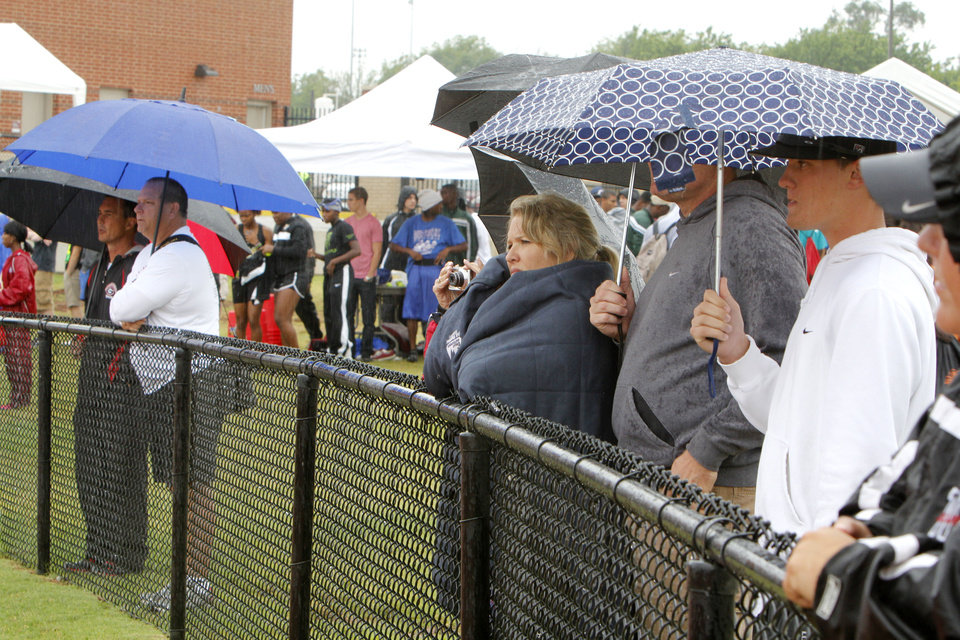 Photo - CLASS 5A / CLASS 6A / HIGH SCHOOL TRACK AND FIELD / STATE TOURNAMENT / UMBRELLAS / RAIN: Spectators watch the 5A and 6A state finals track meet at Yukon High School in Yukon, OK, Friday, May 11, 2012,  By Paul Hellstern, The Oklahoman