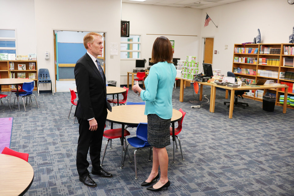 Photo - Principal Michelle Lewis talks about the library with Sen. James Lankford as he takes a tour of Thelma Parks Elementary School in Oklahoma City looking at the RESTORE OKC program there Tuesday, October 8, 2019. [Doug Hoke/The Oklahoman]