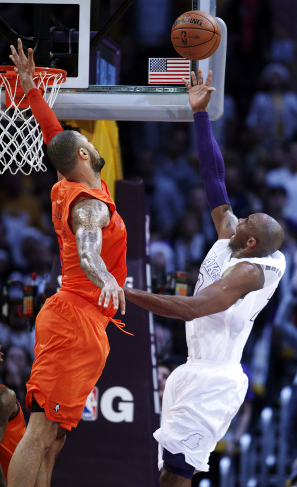 Photo - Los Angeles Lakers guard Kobe Bryant, right, shoots against New York Knicks center Tyson Chandler, left, during the second half of their NBA basketball game in Los Angeles, Tuesday, Dec. 25, 2012. The Lakers won 100-94. (AP Photo/Alex Gallardo)