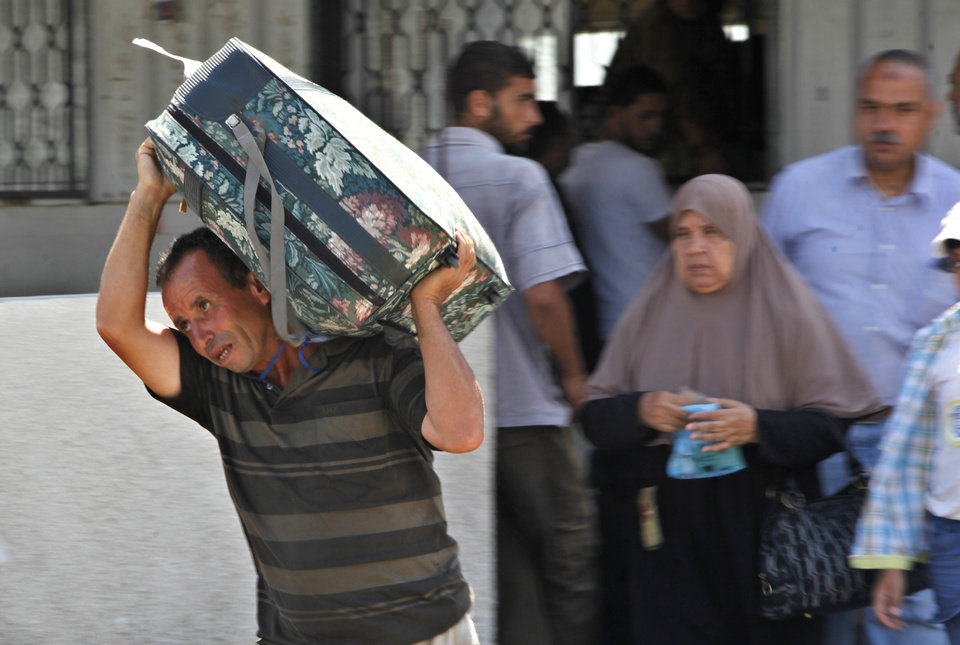 Photo - A Palestinian man carries a luggage to the bus at the border between the Gaza Strip and Egypt, in Rafah, southern Gaza Strip, Wednesday, July 24, 2013. Egypt has sealed smuggling tunnels and blocked most passenger traffic in the toughest border restrictions on the Gaza Strip in recent years, causing millions of dollars in economic losses and prompting concerns among Gaza's Hamas rulers that the territory is being swept up in the Egyptian military's crackdown on Islamic fundamentalists. (AP Photo/Adel Hana)
