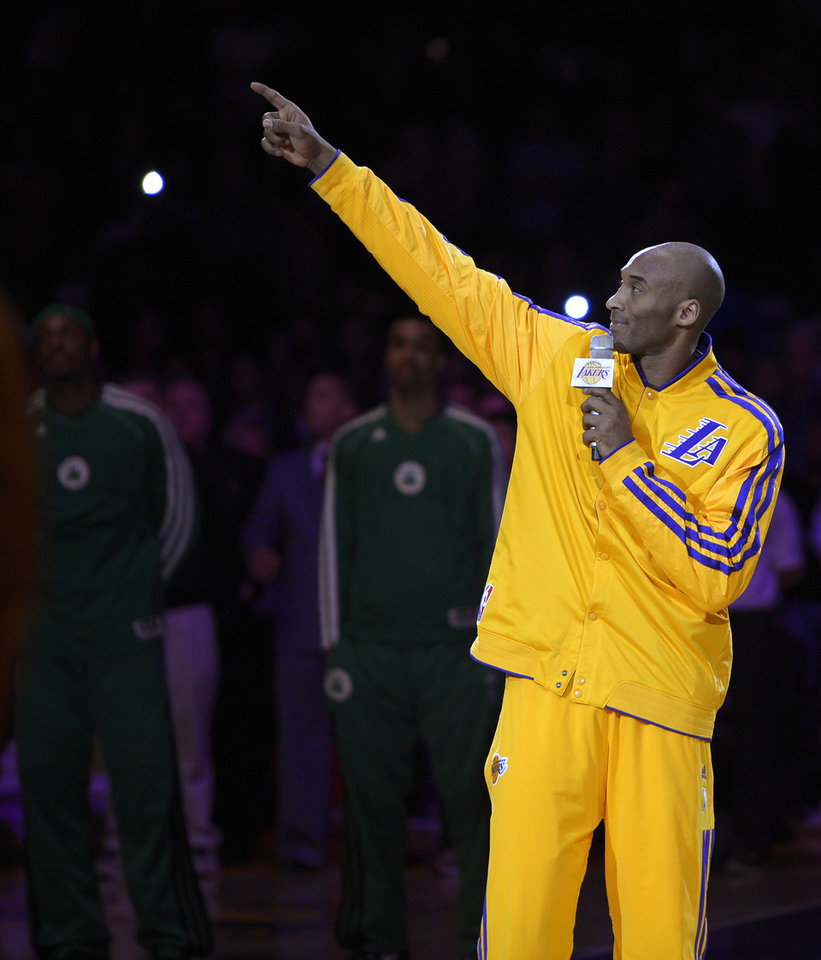 Photo - Los Angeles Lakers' Kobe Bryant point to the Buss family suite during a memorial for late owner Jerry Buss before an NBA basketball game between the Lakers and the Boston Celtics, Wednesday, Feb. 20, 2013, in Los Angeles. Buss died Monday after a battle with cancer. (AP Photo/Mark J. Terrill)