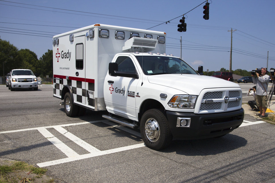 Photo - An ambulance leaves Dobbins Air Reserve Base transporting a second American missionary stricken with Ebola, Tuesday, Aug. 5, 2014, in Marietta, Ga. Nancy Writebol is expected to be admitted to Atlanta's Emory University Hospital on Tuesday, where she will join another U.S. aid worker, Dr. Kent Brantly, in a special isolation unit. (AP Photo/Todd Kirkland)