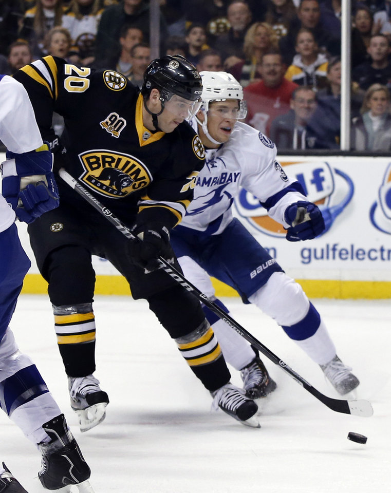 Photo - Boston Bruins left wing Daniel Paille (20) shoots and scores after getting by defenseman Keith Aulie, right, during the second period of an NHL hockey game in Boston Monday, Nov. 11, 2013. The Bruins won 3-0. (AP Photo/Elise Amendola)