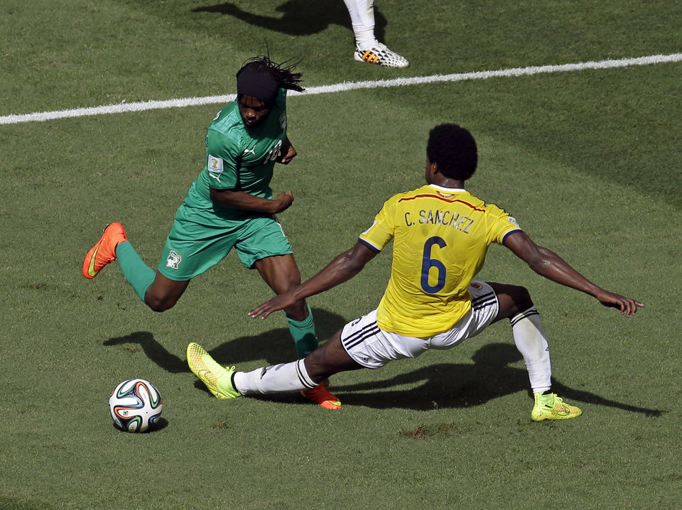 Photo - Ivory Coast's Gervinho dribbles past Colombia's Carlos Sanchez Moreno before scoring during the group C World Cup soccer match between Colombia and Ivory Coast at the Estadio Nacional in Brasilia, Brazil, Thursday, June 19, 2014.  (AP Photo/Themba Hadebe)