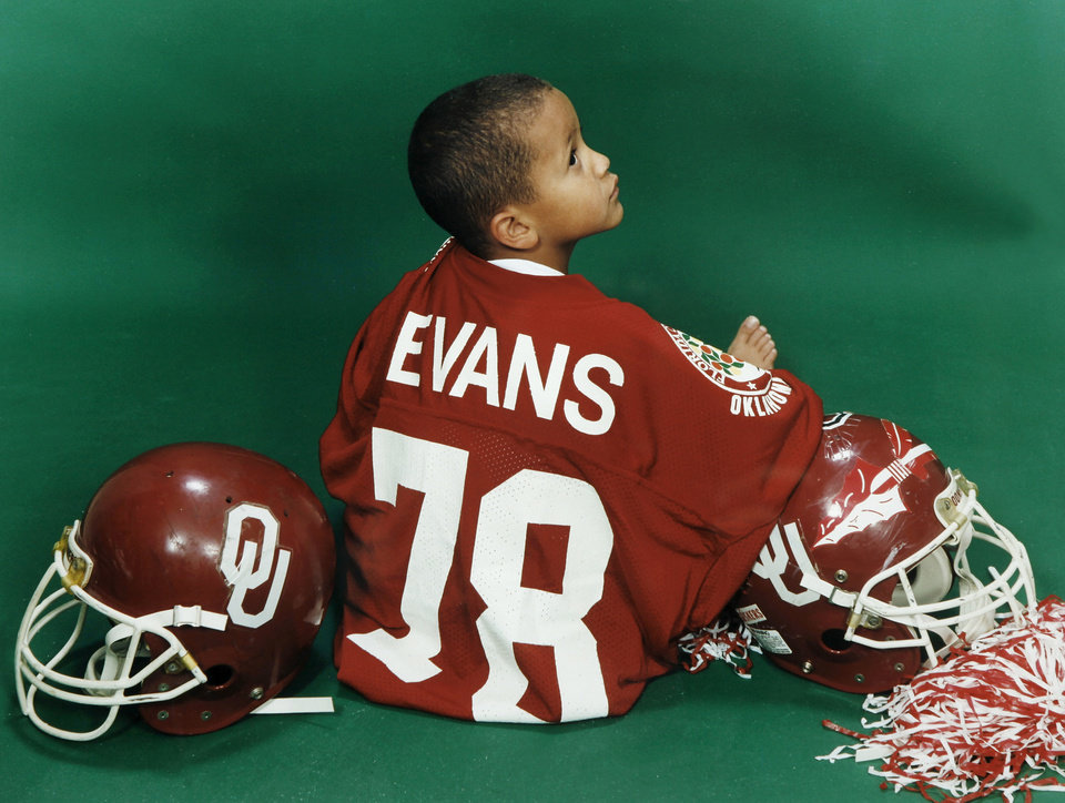 Photo - A portrait of Jordan Evans, wearing his dad's jersey from his playing days at the University of Oklahoma.  The photo was taken when Jordan was three years old and it hangs in the office of Jordan's dad, former OU football player Scott Evans.  The framed photo was given to Scott and to his dad as a gift. Photo by Jim Beckel, The Oklahoman