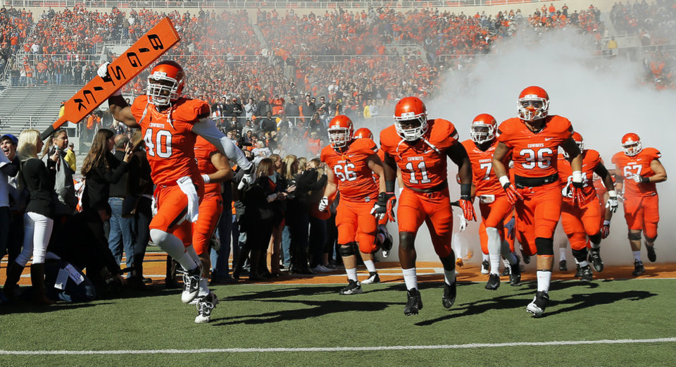 Photo - OSU takes the field before a college football game between the Oklahoma State University Cowboys (OSU) and the Texas Christian University Horned Frogs (TCU) at Boone Pickens Stadium in Stillwater, Okla., Saturday, Oct. 19, 2013. Photo by Nate Billings, The Oklahoman