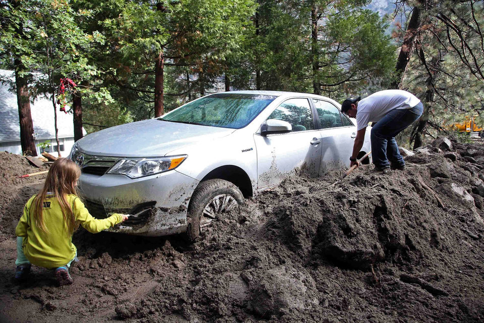 Photo - Andrew Watson and his daughter Taylor Becker dig out their car after rocks and mud inundated their home in the mountain community of Forest Falls in the San Bernardino Mountains Monday, Aug. 4, 2014. Crews cleared roads in an area where some 2,500 had been stranded after thunderstorms caused mountain mudslides in Southern California over the weekend, while authorities estimated that between 6 and 8 homes were badly damaged and likely uninhabitable. One person was found dead in a vehicle that was caught in a flash flood. A group of campers spent the night at a community center near Forest Falls headed. (AP Photo/Nick Ut)