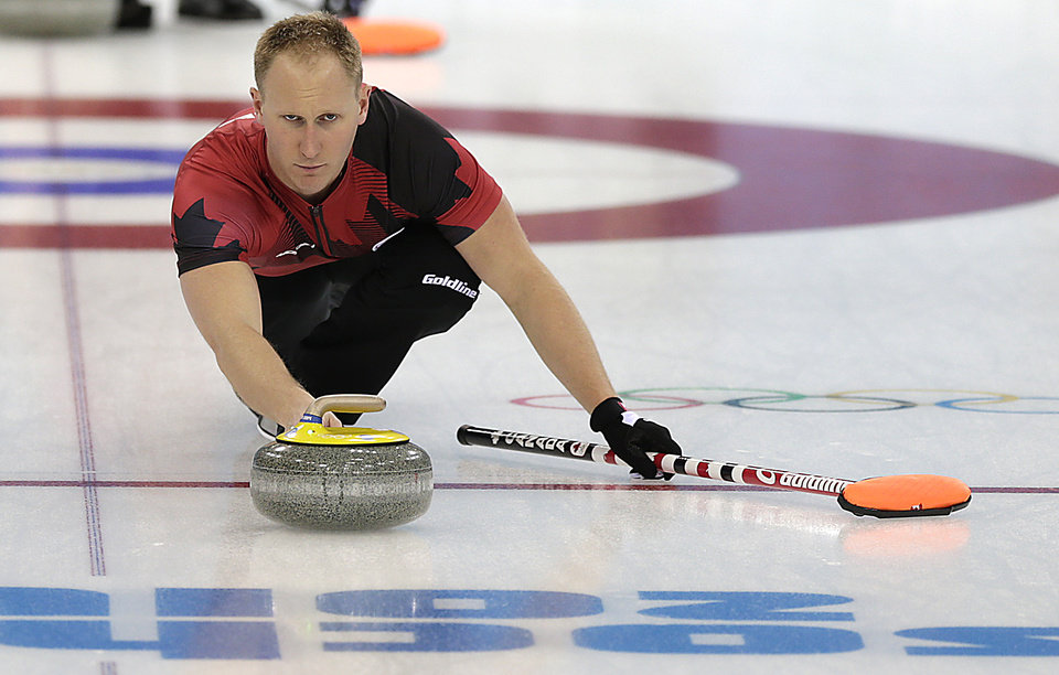Photo - Canada's Brad Jacobs delivers the rock during the men's curling training session at the 2014 Winter Olympics, Sunday, Feb. 9, 2014, in Sochi, Russia. (AP Photo/Wong Maye-E)