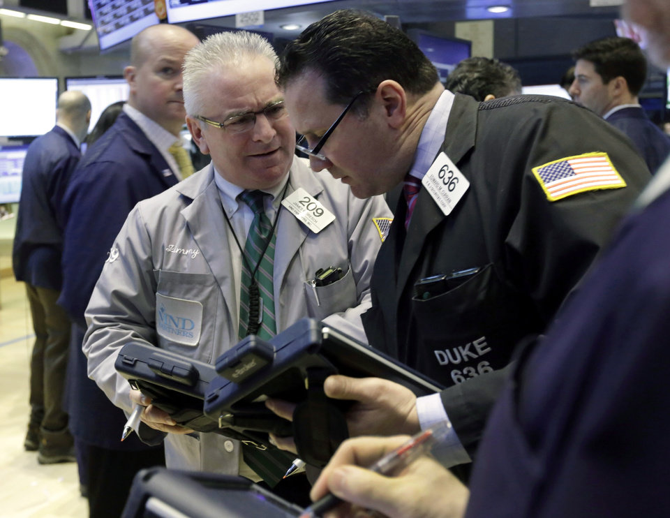 Photo - Traders James Dresch, second left, and Edward Curran, right, confer on the floor of the New York Stock Exchange Tuesday, Jan. 22, 2013. Stocks are wavering in early trading on Wall Street as U.S. companies turn in a mixed batch of earnings reports. (AP Photo/Richard Drew)