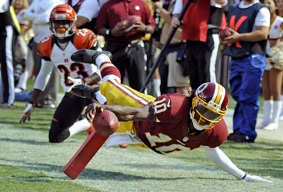 Photo -   ADVANCE FOR WEEKEND EDITIONS, OCT. 20-21 - FILE - This Sept. 23, 2012 file photo shows Washington Redskins quarterback Robert Griffin III being knocked out of bounds just shy of the goal line during an NFL game against the Cincinnati Bengals, in Landover, Md. Some quarterbacks take the safe approach. Others get lost in trying to fight for that extra yard. (AP Photo/Nick Wass, File)