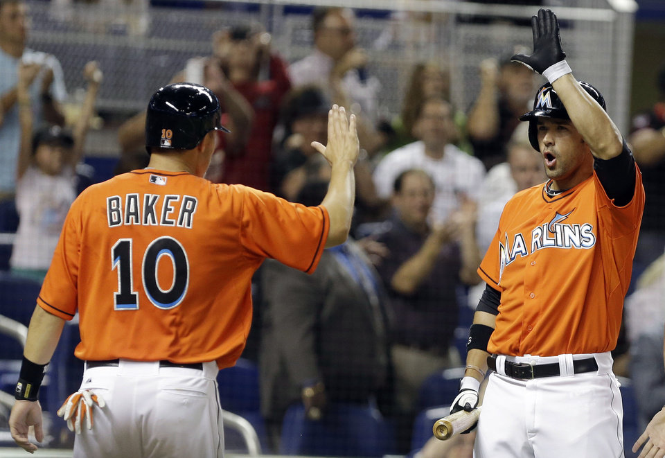 Photo - Miami Marlins' Jeff Baker (10) is met by Garrett Jones after scoring on a double hit by Casey McGehee in the fifth inning of an opening day baseball game, Monday, March 31, 2014, in Miami. (AP Photo/Lynne Sladky)