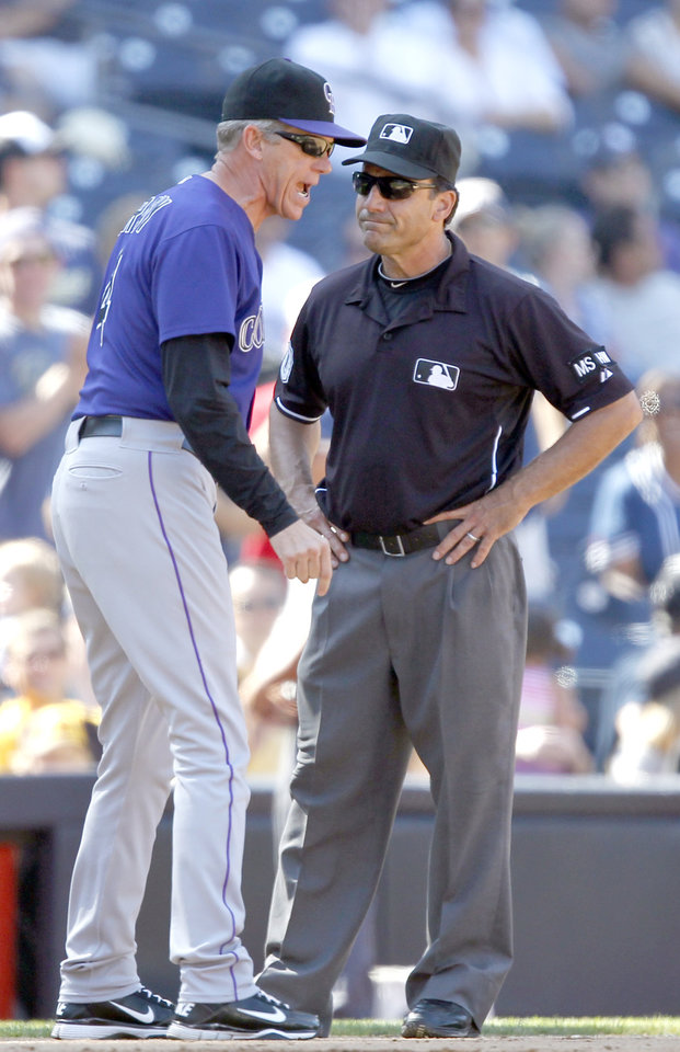 Photo -   Colorado Rockies manager Jim Tracy, left, argues with third base umpire Phil Cuzzi on a safe call that went for the San Diego Padres during the ffith inning of their baseball game in San Diego, Sunday, Sept. 16, 2012. (AP Photo/Alex Gallardo)