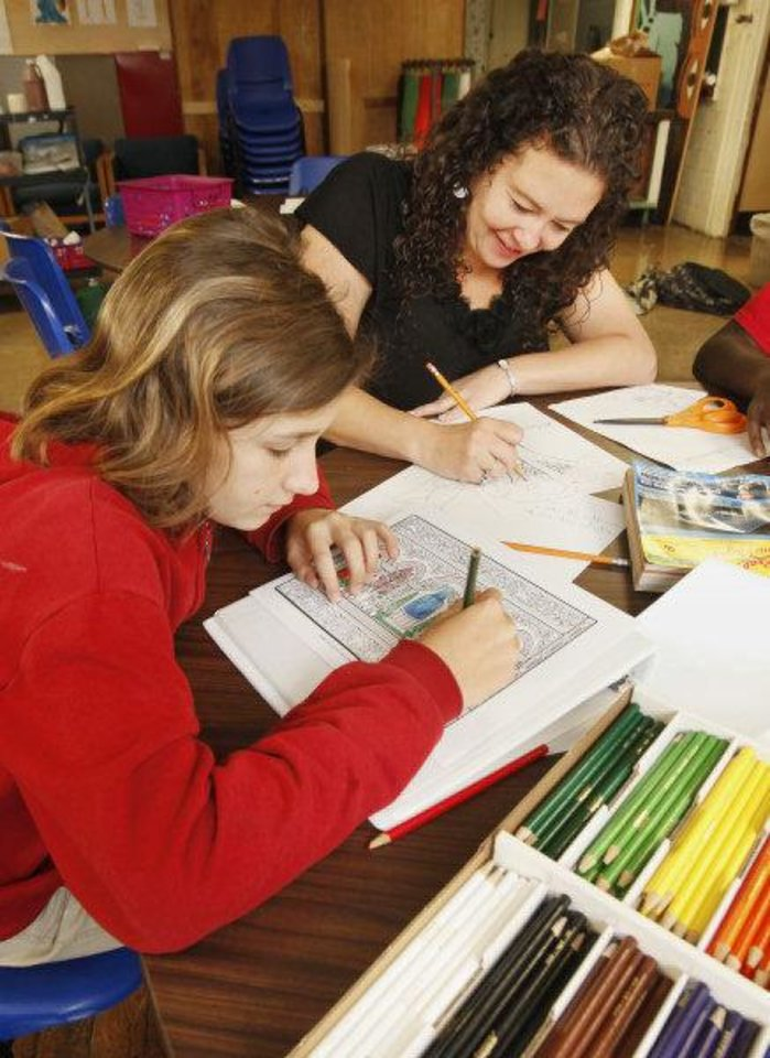Photo - Karley Carter, 12, and chruch volunteer Lechelle Calderwood, work on art projects during the
