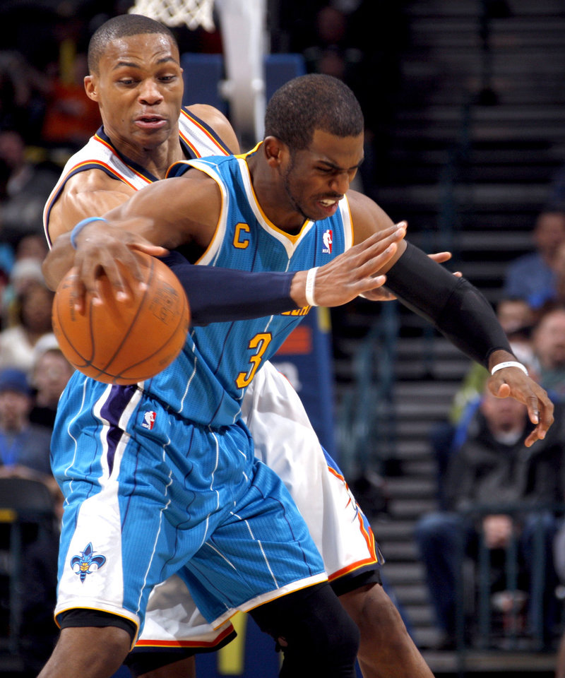 Photo - Oklahoma City's Russell Westbrook (0) tries to steal the ball from New Orleans' Chris Paul (3) during the NBA basketball game between Oklahoma City Thunder and New Orleans Hornet, Wednesday, Feb. 2, 2011 at the Oklahoma City Arena. Photo by Sarah Phipps, The Oklahoman