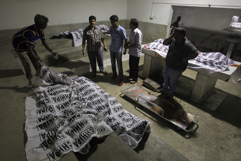 Photo - Volunteers look at dead bodies of people killed during an attack by unknown gunmen on Jinnah International Airport, Sunday night, June 8, 2014, in Karachi, Pakistan. Gunmen disguised as police guards stormed an airport terminal used for VIPs and cargo in Pakistan's largest city Sunday night, killing at least nine people as explosions echoed into the night, officials said.  (AP Photo/Fareed Khan)