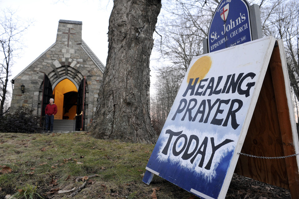 Photo - A sign for a Healing Prayer stands outside St. John's Episcopal Church near the scene of a school shooting in Newtown, Conn., Friday, Dec. 14, 2012.  A man opened fire Friday inside two classrooms at the school where his mother worked as a teacher, killing 26 people, including 20 children.  The killer, armed with two handguns, committed suicide at the school and another person was found dead at a second scene, bringing the toll to 28, authorities said. A law enforcement official identified the gunman as 20-year-old Adam Lanza.  (AP Photo/Jessica Hill)