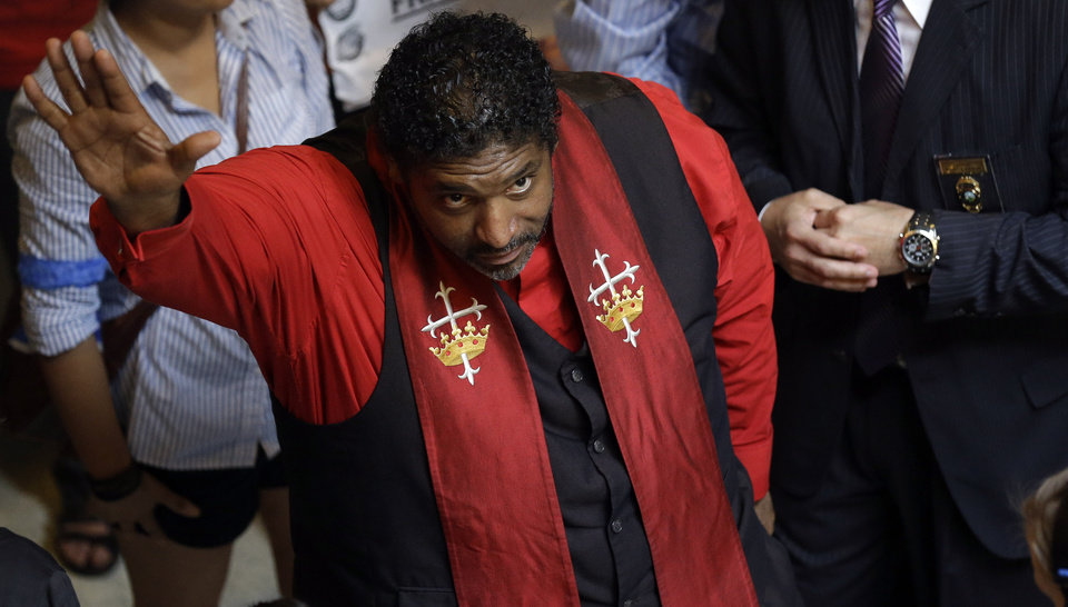 Photo - Rev. William Barber, president of the N.C. chapter of the The National Association for the Advancement of Colored speaks to supporters at the state legislature in Raleigh, N.C., Monday, June 17, 2013. Supporters of what the group calls