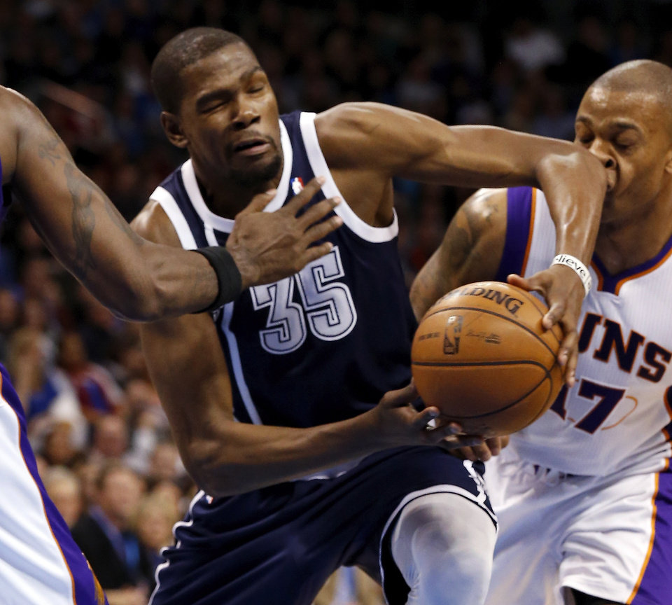 Photo - Oklahoma City Thunder's Kevin Durant (35) drives past Phoenix Suns' P.J. Tucker (17) as the Oklahoma City Thunder play the Phoenix Suns in NBA basketball at the Chesapeake Energy Arena in Oklahoma City, on Monday, Dec. 31, 2012.  Photo by Steve Sisney, The Oklahoman