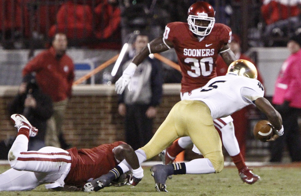 Photo -   Oklahoma defensive back Gabe Lynn (9) tackles Notre Dame quarterback Everett Golson (5) during the second half of an NCAA college football game in Norman, Okla., Saturday, Oct. 27, 2012. Notre Dame won 30-13. (AP Photo/Alonzo Adams)
