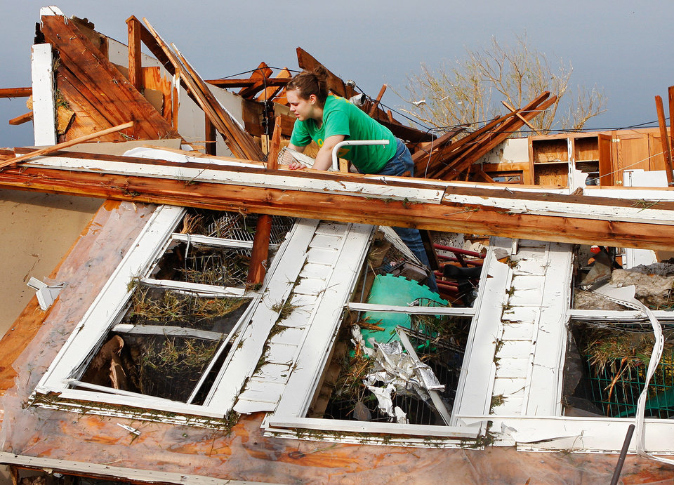 Photo - Rebecca Apel, 15, climbs on top of what remains  of her family's home on SH 74 east of Cashion. She was looking for her birds; she located the cage and is trying to remove it from behind this toppled west wall of the house.  Her home was demolshed when a tornado came through the area lateTuesday afternoon,  May 24, 2011,   Photo by Jim Beckel, The Oklahoman
