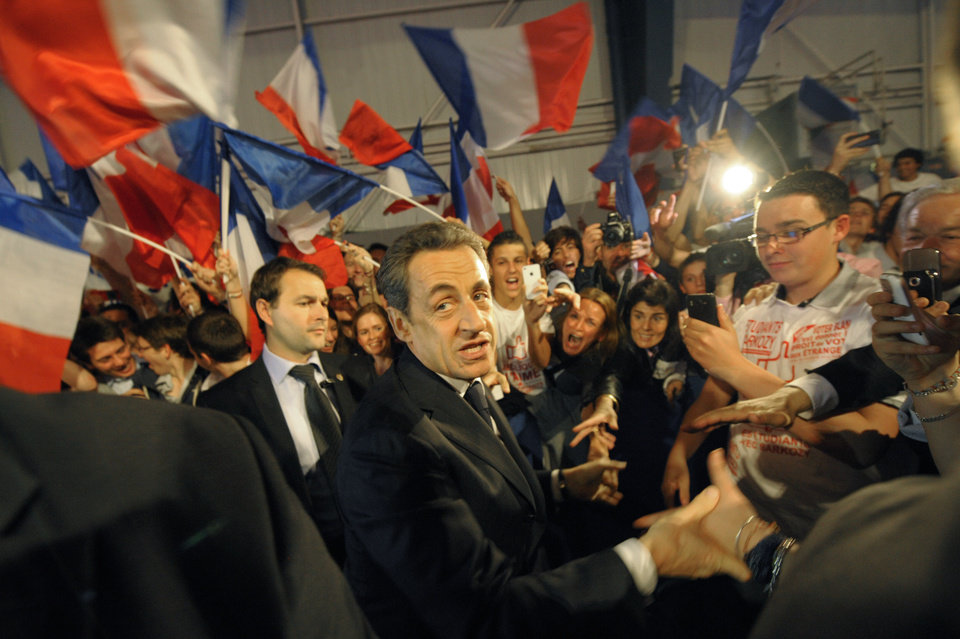Photo -   France's President and candidate for re-election in 2012, Nicolas Sarkozy, shakes hands as he arrives for a campaign meeting in Toulouse, western France, Sunday, April 29, 2012. (AP Photo/Philippe Wojazer, Pool)