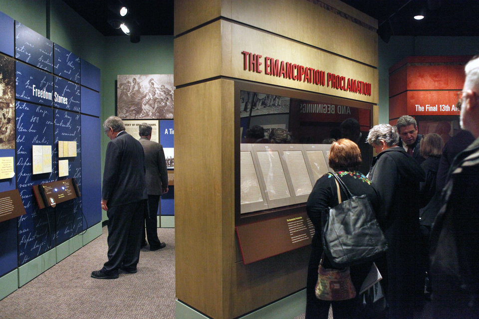 FILE - This Nov 4, 2010 file photo shows National Archives visitors looking at a display of President Abraham Lincoln's Emancipation Proclamation at the National Archives in Washington. As New Year's Day approached 150 years ago, all eyes were on Lincoln in expectation of what he warned 100 days earlier would be coming _ his final proclamation declaring all slaves in states rebelling against the Union to be �forever free.� A tradition began on Dec. 31, 1862, as many black churches held Watch Night services, awaiting word that Lincoln's Emancipation Proclamation would take effect as the country was in the midst of a bloody Civil War. Later, congregations listened as the president's historic words were read aloud.  (AP Photo/Jacquelyn Martin, File)