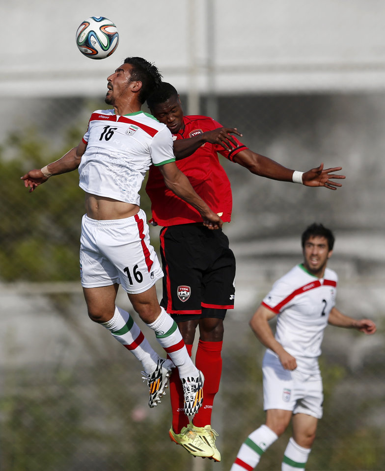 Photo - Iran's Reza Ghouchannejad, left, and Trinidad's Sheldon Bateau go up for the ball during the first half of an international soccer friendly at the Corinthians soccer team training center Sao Paulo, Brazil, on Sunday, June 8, 2014. Iran will play in group F of the 2014 soccer World Cup. (AP Photo/Julio Cortez)