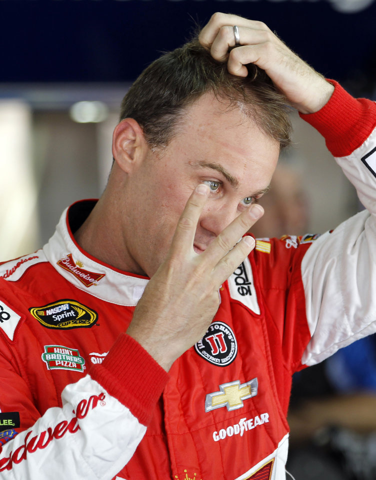 Photo - Kevin Harvick talks to a crew member before practice for Sunday's NASCAR Sprint Cup series Coca-Cola 600 auto race at Charlotte Motor Speedway in Concord, N.C., Thursday, May 22, 2014. (AP Photo/Terry Renna)