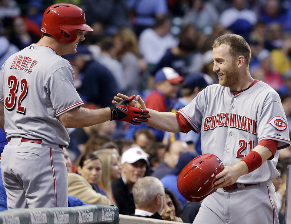 Photo - Cincinnati Reds' Todd Frazier, right, celebrates with Jay Bruce after scoring on a double hit by Joey Votto during the sixth inning of a baseball game against the Chicago Cubs in Chicago, Wednesday, June 25, 2014. (AP Photo/Nam Y. Huh)