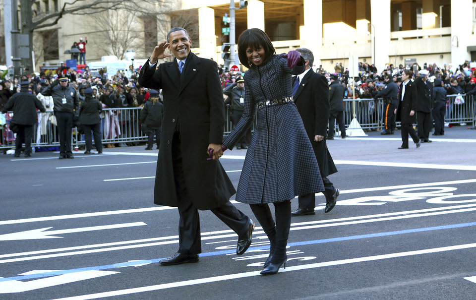 Photo - President Barack Obama and first lady Michelle Obama wave as they walk down Pennsylvania Avenue in Washington, Monday, Jan. 21, 2013, during the Inaugural Parade after his ceremonial swearing-in on Capitol Hill during the 57th Presidential Inauguration. (AP Photo/The New York Times, Doug Mills, Pool) ORG XMIT: NYNYT303