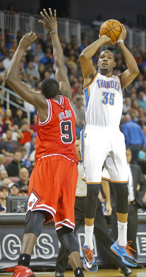 Oklahoma City Thunder's Kevin Durant (35) shoots for three points against Chicago Bulls' Luol Deng (9) in the second quarter during their preseason NBA basketball game in Wichita, Kan., Wednesday, Oct. 23, 2013. (AP Photo/The Wichita Eagle, Fernando Salazar) LOCAL TV OUT; MAGAZINES OUT; LOCAL RADIO OUT; LOCAL INTERNET OUT