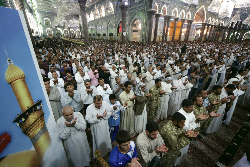 Photo - Shiite Muslim worshippers pray at the holy shrine of Imam Hussein during Friday prayers in the Shiite holy city of Karbala, 50 miles  (80 kilometers) south of Baghdad, Iraq, Friday, July 11, 2014. The Sunni militant blitz led by the Islamic State extremist group has effectively cleaved the country along ethnic and sectarian lines — the swath of militant-held Sunni areas, the Shiite-majority south and center ruled by the Shiite-led government in Baghdad and the Kurdish north. (AP Photo)