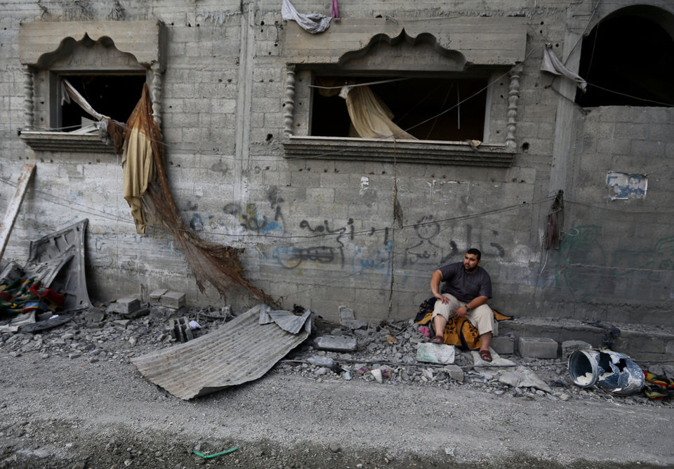 Photo - A Palestinian sits in front of the damaged house of Gaza's police chief Taysir al-Batsh after it was hit by an Israeli missile strike in Gaza City, Sunday, July 13, 2014. The strike that hit the home and damaged a nearby mosque as evening prayers ended Saturday, killed at least 18 people, wounded 50 and some people are believed to be trapped under the rubble, said Palestinian Health Ministry official Ashraf al-Kidra. (AP Photo/Hatem Moussa)