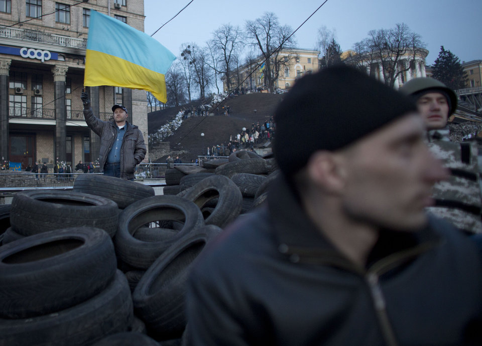 Photo - An anti-government protester raises the Ukrainian flag at a barricade in central Kiev, Ukraine, Friday, Feb. 21, 2014. European officials say Ukrainian protesters have agreed to a deal with Ukraine's president on defusing a deadly political crisis. Earlier Friday President Viktor Yanukovych announced early elections and promised to invite the opposition into the government. (AP Photo/Darko Bandic)