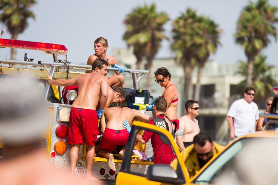 Photo - CORRECTS SPELLING Lifeguards assist a person who was in the water  Sunday July 27, 2014 in Los Angeles. Authorities said lightning struck 14 people, leaving two critically injured, as rare summer thunderstorms swept through Southern California on Sunday. (AP Photo/Steve Christensen)