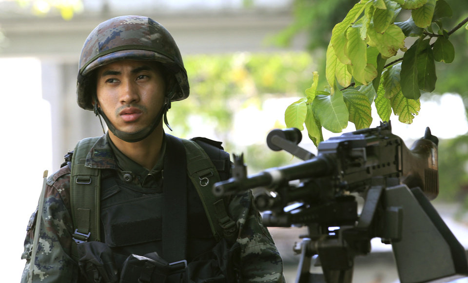 Photo - A Thai soldier stands guard outside the Thai police headquarters Tuesday, May 20, 2014, in Bangkok, Thailand. Thailand's army declared martial law before dawn Tuesday in a surprise announcement it said was aimed at keeping the country stable after six months of sometimes violent political unrest. The military, however, denied a coup d'etat was underway.  (AP Photo/Sakchai Lalit)