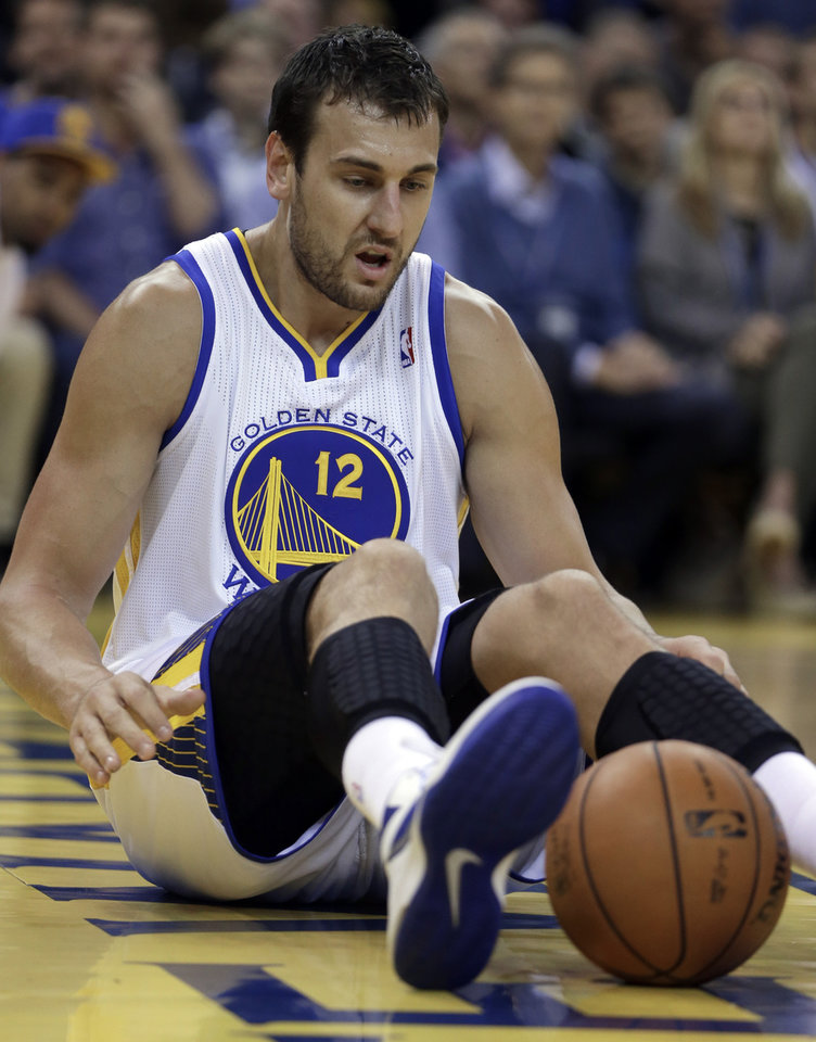 Photo - Golden State Warriors' Andrew Bogut sits on the floor during the first half of an NBA basketball game against the Oklahoma City Thunder Thursday, Nov. 14, 2013, in Oakland, Calif. (AP Photo/Ben Margot)