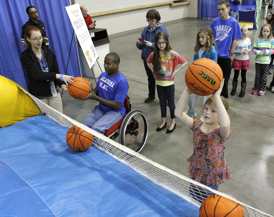 Photo - Participants try and shoot baskets during Bart & Nadia's Sports & Health Festival at the Cox Convention Center in Oklahoma City, OK, Saturday, February 16, 2013,  By Paul Hellstern, The Oklahoman