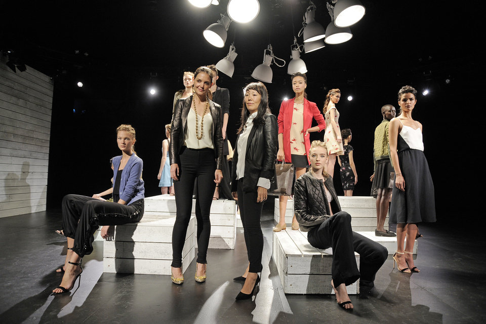 Photo -   In this photo provided by Holmes & Yang, Katie Holmes, center left, and Jeanne Yang, center right, pose for a portrait in front of the Holmes & Yang Spring 2013 collection during Fashion Week in New York, Tuesday, Sept. 11, 2012. (AP Photo/Holmes & Yang, Dan Ashby)