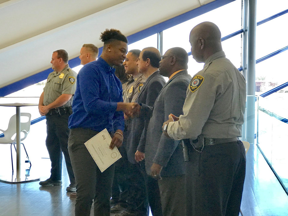 Photo -  Damian Byest, of Moore, shakes hands with the Rev. Corey Smith, guest speaker at the recent graduation for the Oklahoma City Police Department's Juvenile Intervention Program held at the Devon Boathouse. [Photo by Carla Hinton, The Oklahoman]